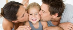 Father and mother kissing daughter