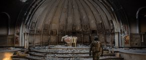 QARAQOSH, IRAQ - NOVEMBER 08:  A fighter from the NPU (Nineveh Plain Protection Units) waks through a destroyed church on November 8, 2016 in Qaraqosh, Iraq. The NPU is a military organization made up of Assyrian Christians and was formed in late 2014 to defend against ISIL. Qaraqosh, a largely Assyrian City just 32km southeast of Mosul was taken by ISIL in August, 2014 forcing all residents to flee, the town was largely destroyed with all of the churches burned or heavily damaged. The town stayed under ISIL control last week when it was liberated during the Mosul Offensive.  (Photo by Chris McGrath/Getty Images)