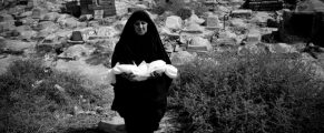 Iraq, Basra, 24 April 2012 - An old woman, Undertaker, wears the linen-wrapped body of a child in the children's graveyard for burial in Basrah.