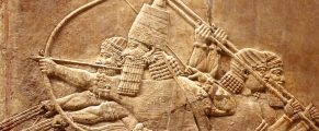 Assyrian relief on the wall. Ancient carving on the stone from Middle East history close-up. Remains of the culture of ancient civilization. Assyrian and Sumerian art for vintage background.
