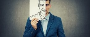Portrait of a sad businessman hiding half his face using a white paper drawn with a fake happy emotion. Mask for hiding the real face expression, create new identity, grey wall background.